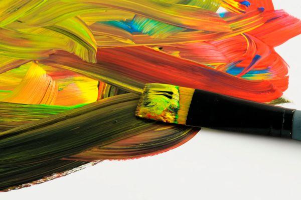 Pincel con pintura acrilica dispersa sobre una superficie lisa.