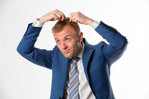 Hombre frente al espejo observando la caída de su pelo