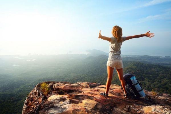 Mujer en la cima de la montaña disfrutando de viajar y trabajar