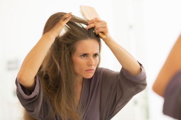 Mujer frente al espejo con indicios de caspa. El enjuague bucal combate este hongo