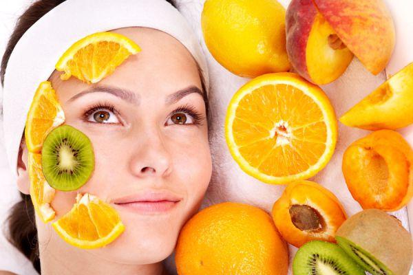 Rostro de mujer con trozos de naranjas, ingrediente para hacer mascarillas naturales para la piel