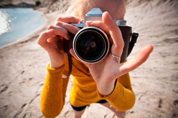 Mujer con cámara fotográfica practicando su hobby en la playa