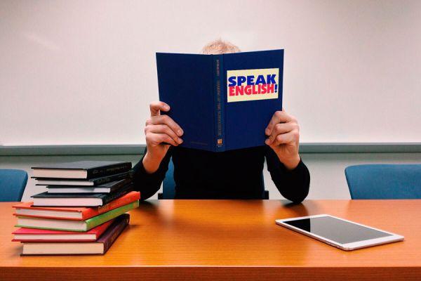 Mujer con libros y tablet estudiando inglés intensivo.