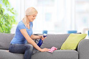 Mujer limpiando muebles de tela con productos caseros