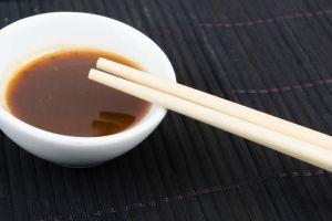 Recipiente con salsa teriyaki casera y palillos chinos