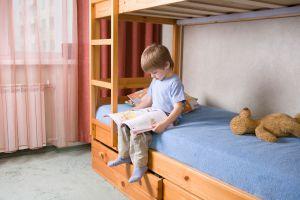 Niño sobre una cama con cajones abajo